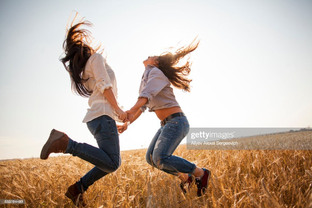 Caucasian women dancing in rural field
