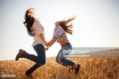 Caucasian women dancing in rural field