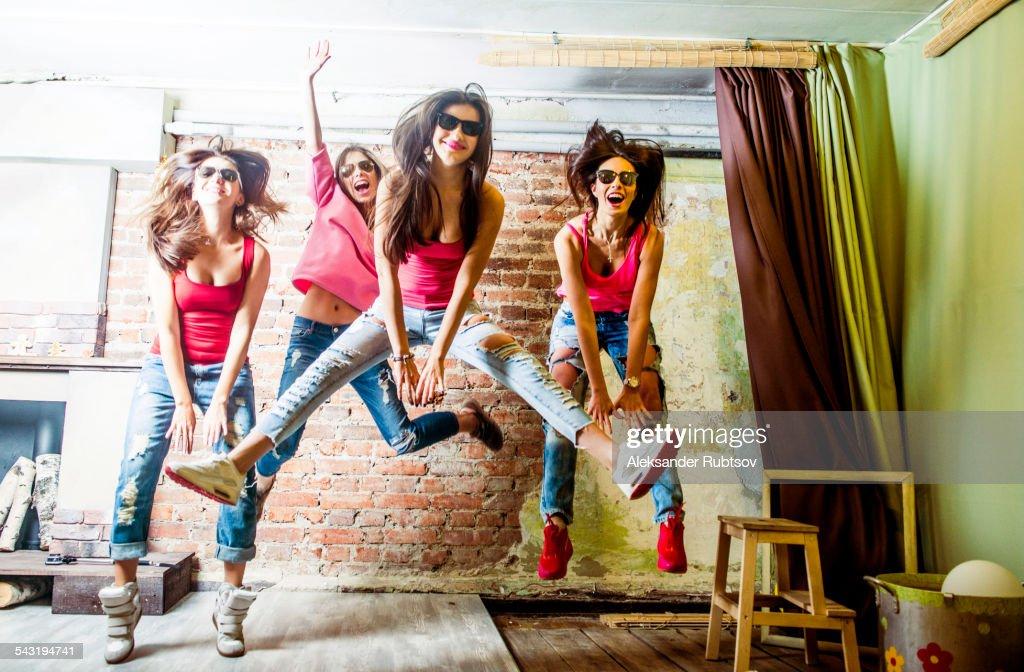 Caucasian women jumping in living room