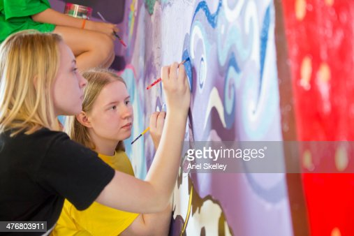 Caucasian women painting mural