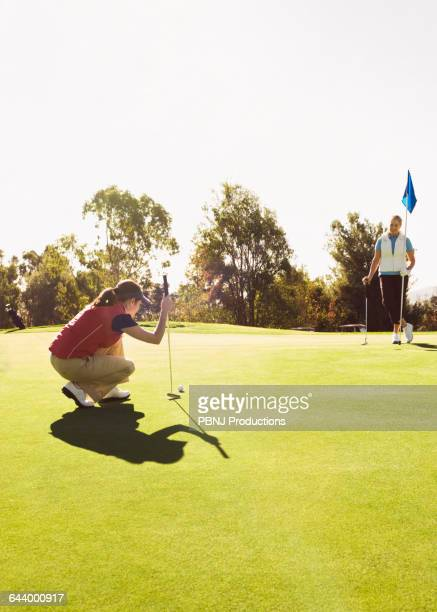 Caucasian women playing golf on golf course