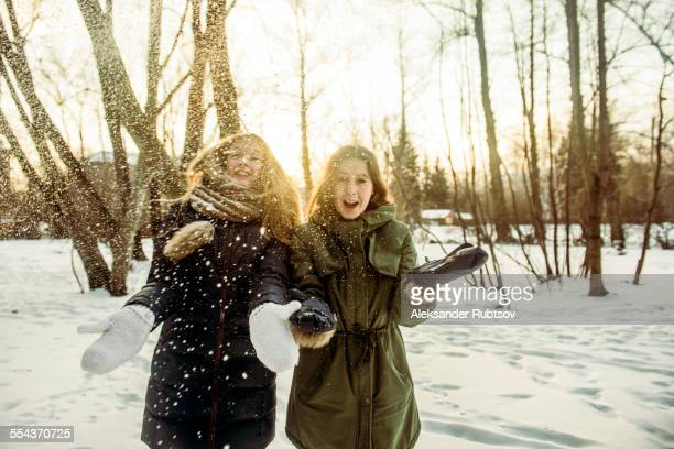 Caucasian women playing in snowy field