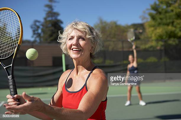 Caucasian women playing tennis on court