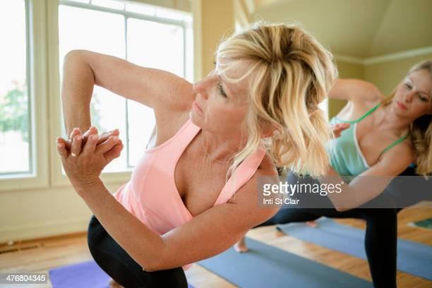 Caucasian women practicing yoga in class