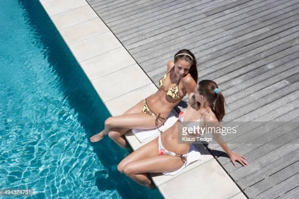 Caucasian women relaxing by swimming pool
