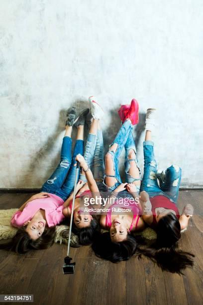 Caucasian women taking cell phone selfie on floor