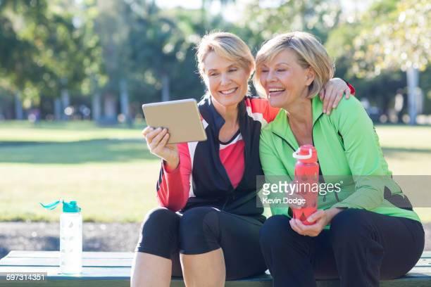Caucasian women using digital tablet in park