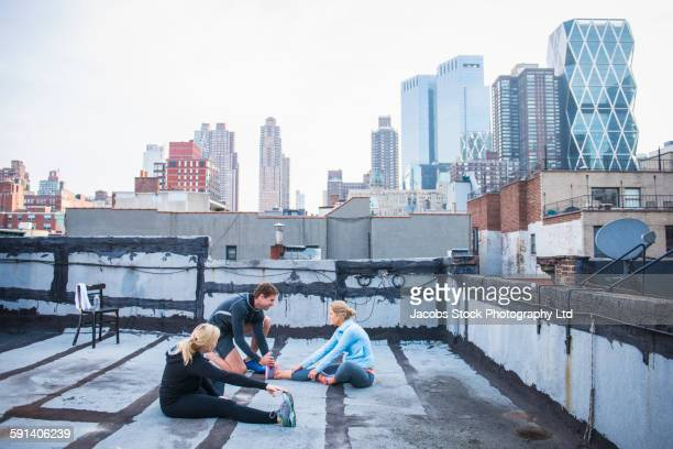 Caucasian women working out with trainer on urban rooftop
