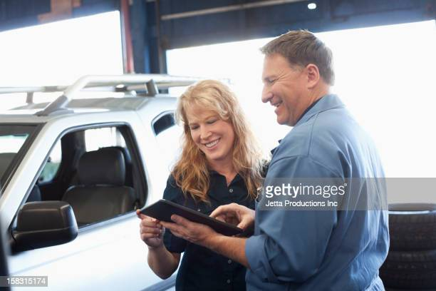 Caucasian worker and customer in auto repair shop
