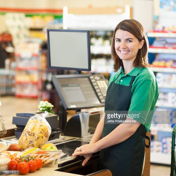 Caucasian worker at register in grocery store