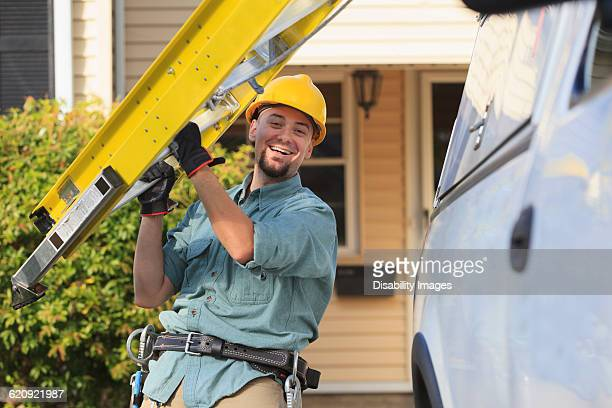 Caucasian worker carrying ladder