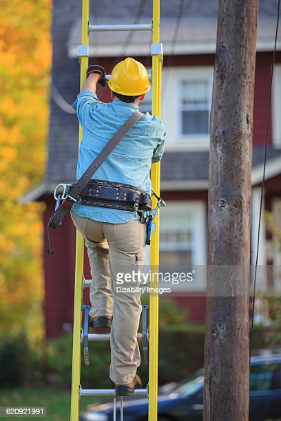 Caucasian worker climbing ladder at tree