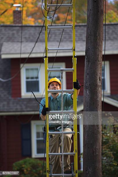 Caucasian worker climbing ladder
