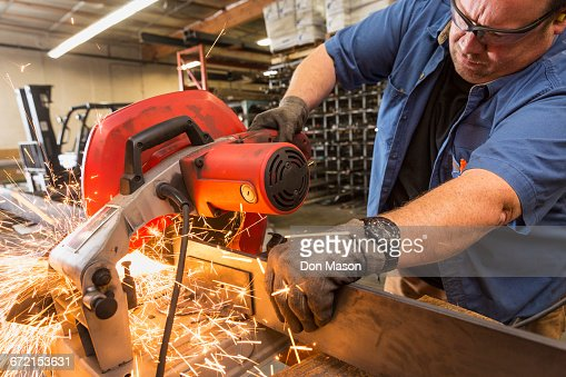 Caucasian worker cutting metal in factory
