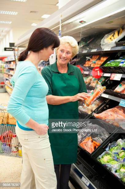 Caucasian worker helping shopping woman in grocery store