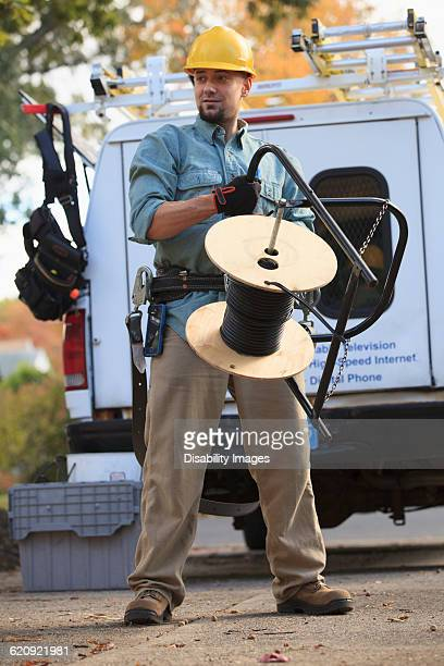 Caucasian worker holding cable spool