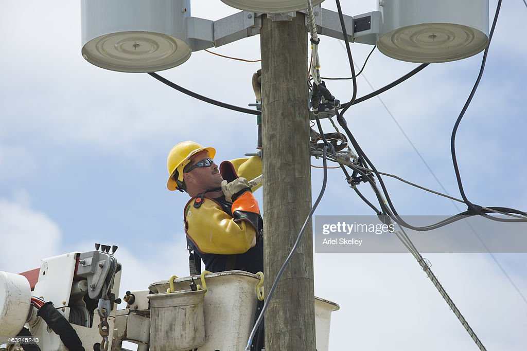Caucasian worker in cherry picker at power line