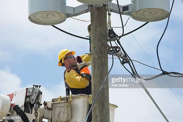 Caucasian worker in cherry picker at power line