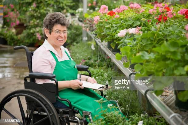 Caucasian worker in wheelchair working in nursery