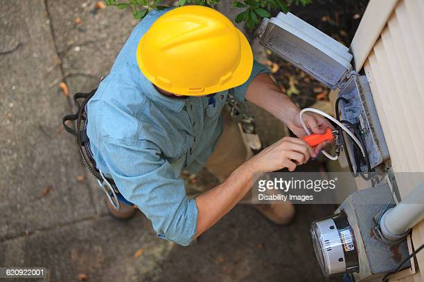 Caucasian worker installing cable box