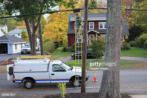 Caucasian worker installing cable on pole