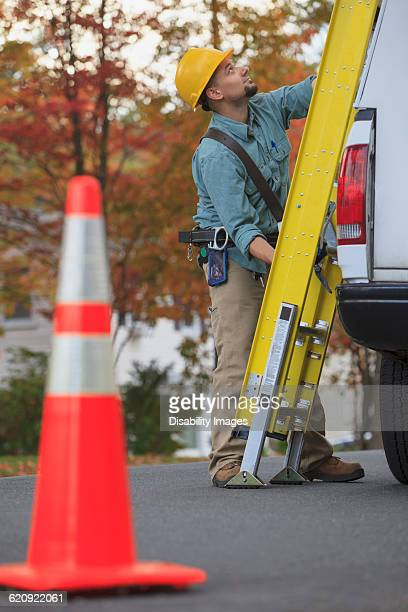 Caucasian worker loading ladder on truck