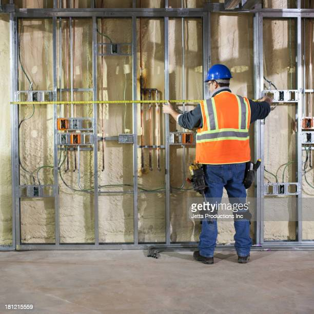 Caucasian worker measuring metal on site