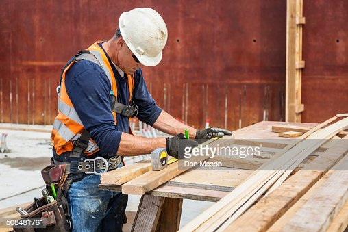 Caucasian worker measuring wood at construction site