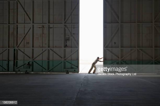 Operaio caucasico apertura grande magazzino porta