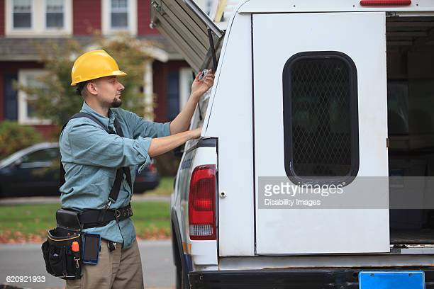 Caucasian worker pulling equipment from truck