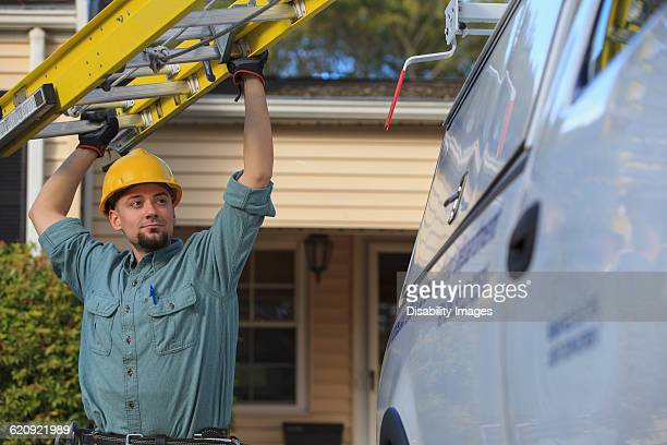 Caucasian worker pulling ladder from truck roof