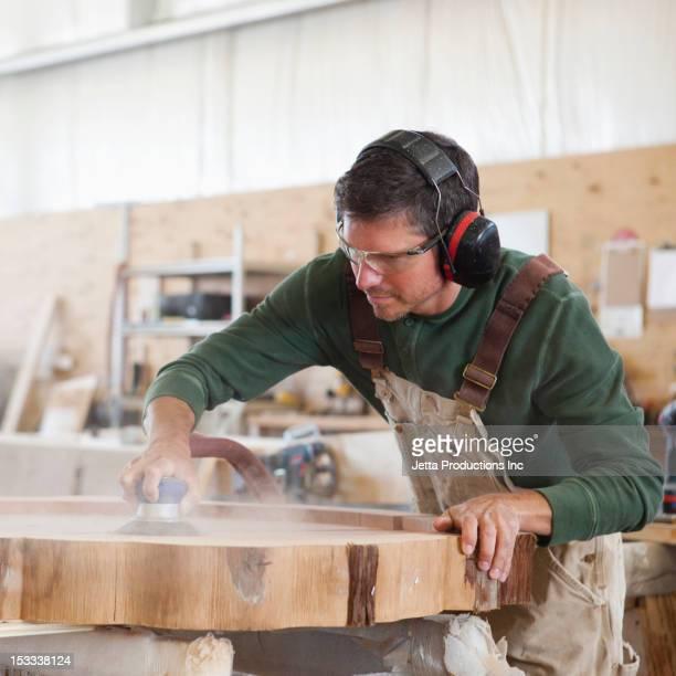 Caucasian worker sanding wood in factory