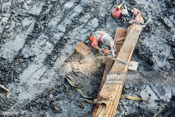 Caucasian worker sawing wood at construction site