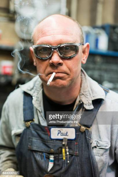 Caucasian worker smoking cigarette in factory