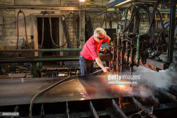 Caucasian worker spraying machinery in factory
