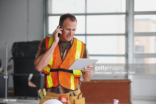 Caucasian worker talking on cell phone and using digital tablet