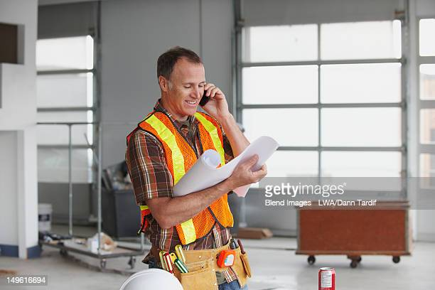 Caucasian worker talking on cell phone on construction site