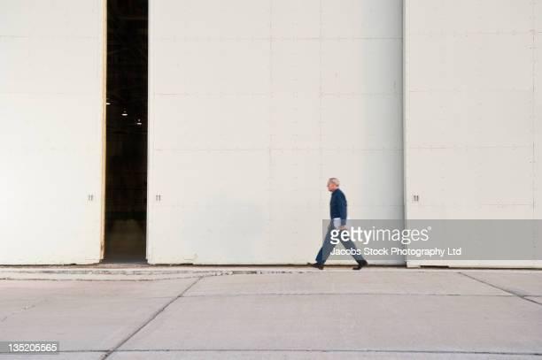 Kaukasier Arbeiter zu Fuß vorbei an Lager Tür