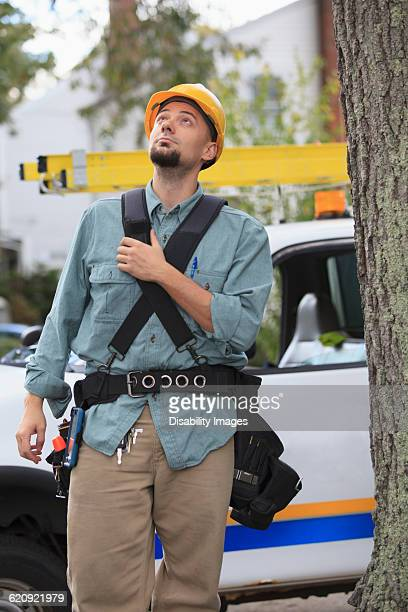 Caucasian worker walking under tree
