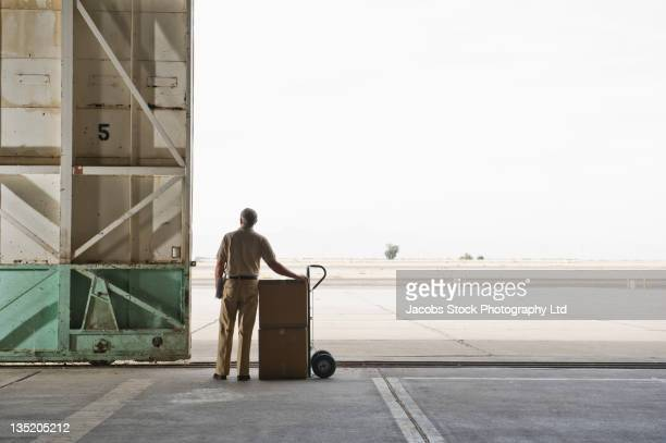 Caucasian worker with boxes in empty warehouse