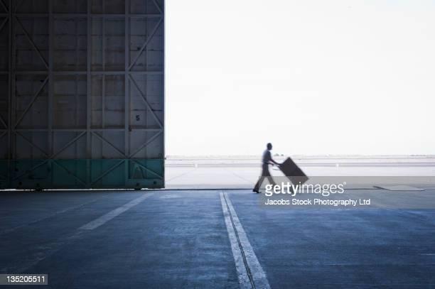 Europäischer Abstammung Arbeiter mit Boxen in leere Lager