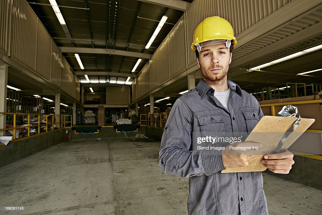 Caucasian worker with clipboard in warehouse : Stock Photo