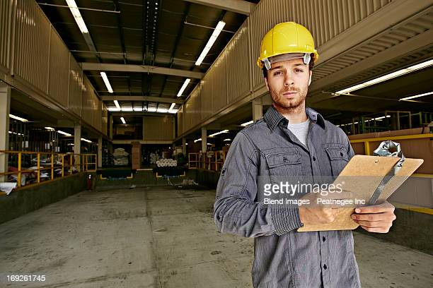 Caucasian worker with clipboard in warehouse