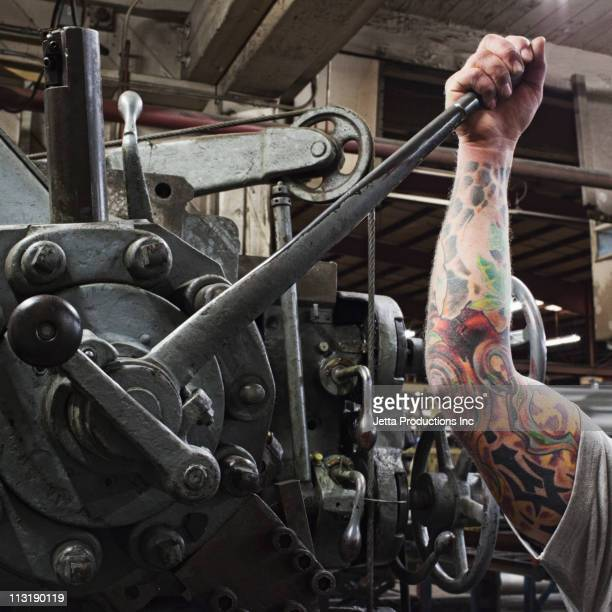 Caucasian worker with tattoos pulling lever in factory