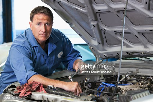 Caucasian worker working on automobile engine