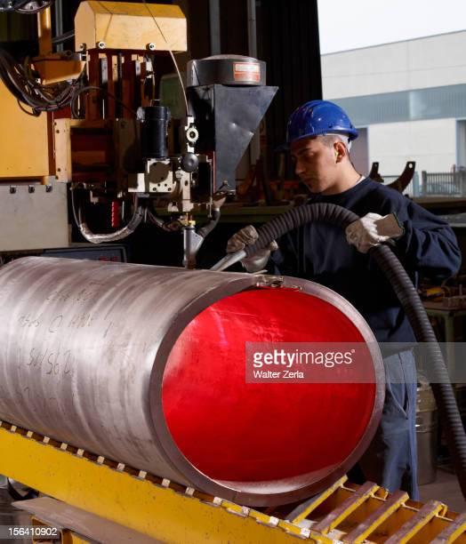 Caucasian worker working on steel pipe in factory