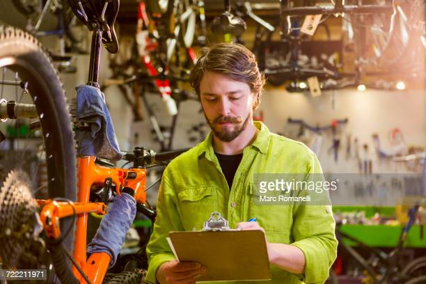 Caucasian worker writing on clipboard in bicycle shop