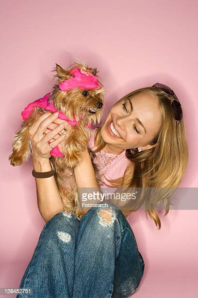 Caucasian young adult female holding Yorkshire Terrier dog.
