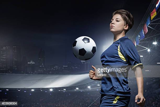 Caucasian young adult female soccer player playing football in stadium