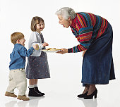 caucasian young kids get cookies from grandma and giggle
